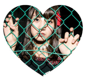 Heart-shaped Christmas ornament of Guso Drop's Saki behind a fence where she belongs